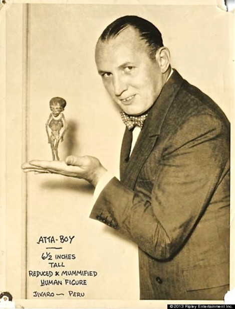 Robert Ripley holding a tiny, mysterious mummy
